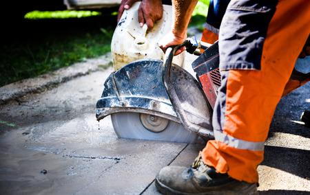 Photo pour Construction worker cutting Asphalt paving stabs for sidewalk using a cut-off saw. - image libre de droit