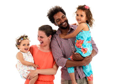 Happy interracial family is celebrating, laughing and having fun with Hispanic African American Father, Caucasian mother and Mulatto children daughters.  Isolated on white.の写真素材