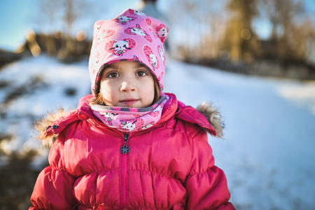 Little girl in winter clothes standing in mountain ski resort. A child with cap, scarf and winter jacket is looking at the camera outside in snowy nature.