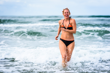 Foto de Woman enjoying the sea and waves of Atlantic ocean. Mature, mid aged, young attractive woman in bathing suit bikini is running in the ocean sea, playing and sprinkling the water. Atlantic ocean - Portugal. - Imagen libre de derechos