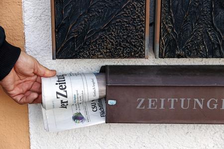 A newspaper deliverer puts the newspaper in the mailbox. Newspaper delivery at the in-house mailbox