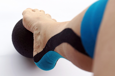 A woman with a tape bandage on her leg doing movement exercises.