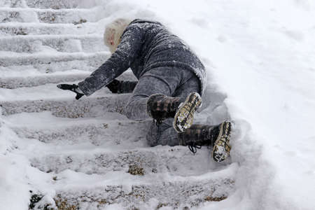 Photo for A woman slipped on the snow-covered stairs and fell - Royalty Free Image