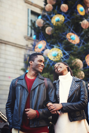 Young African couple in love with beautiful smiles posing against Christmas tree with decorations during walking outdoors in winter day, happy woman and man enjoying recreation time during weekend