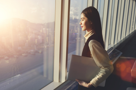 Young woman candidate is holding laptop computer, while standing in office interior and looking out of big window with city view. Female manager with net-book in hand ponder about new business projectの写真素材