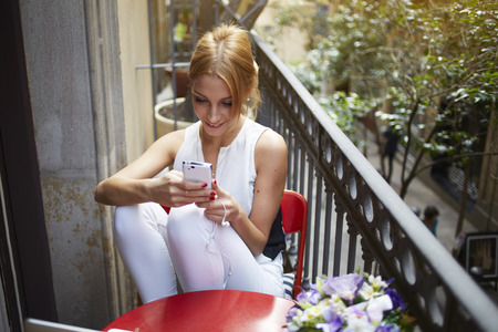 Gorgeous female enjoying recreation time while chatting with her mobile phone on terrace, smiling successful young woman read good news on the smart phone, student hold telephone looking at the screen