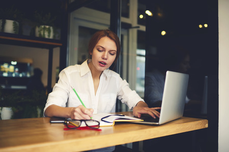 Concentrated female administrative manager using database information from cv of coworkers making financial report of salaries working using laptop computer and wireless connection to internet