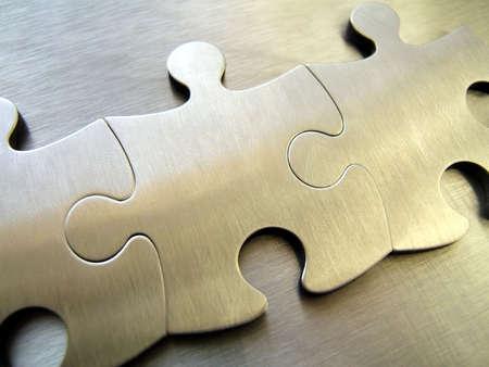 Three metallic jigsaw pieces on a steel background