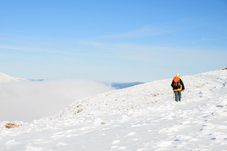 Tourist climbs the snow-covered mountain