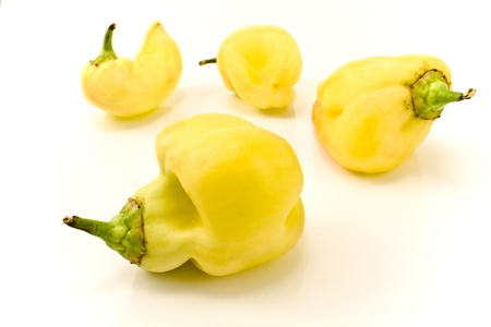 Deformed yellow paprika peppers on white background