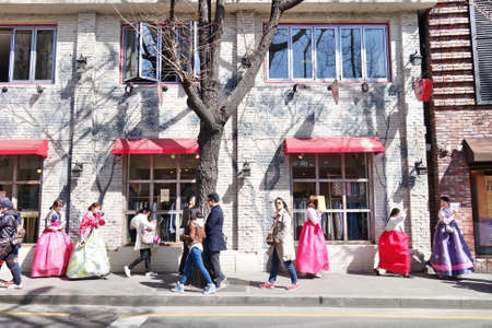 A group of young girls in Korean traditional dress 'Hanbok' are walking along the street of Seoul