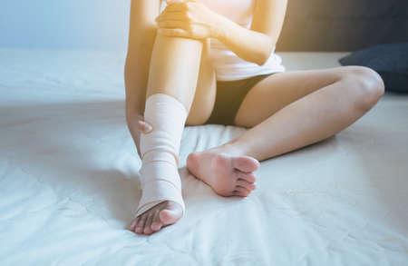 Woman using elastic bandage with foot,Female putting bandage on his injured leg