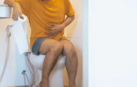 Photo pour Man holding toilet paper and using toilet with suffering from Diarrhea and Hemorrhoids after wake up in morning at home - image libre de droit