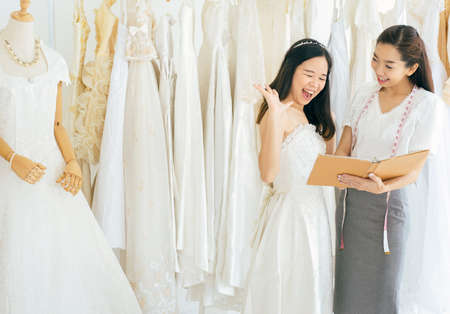 Foto de Portrait of happy asian woman holding credit card in wedding dress store owner,Beautiful female successful dressmaker in shop and small business - Imagen libre de derechos
