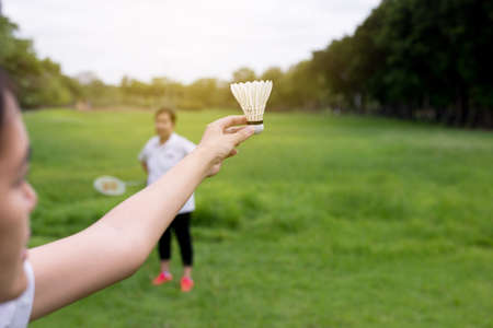 Couple asian woman hands holding badminton racket and shuttlecock in public park,Close up
