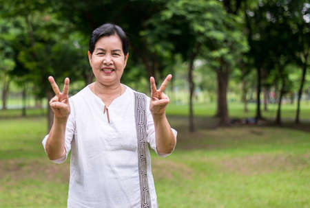 Photo pour Portrait of a elderly asian woman standing and showing peace hand sing at park,Happy and smile face - image libre de droit