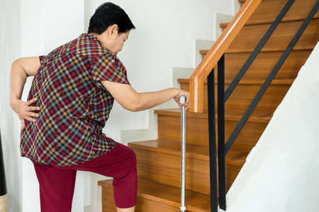 Foto de Asian senior older woman suffering from low-back lumbar pain while walking on stair at home - Imagen libre de derechos
