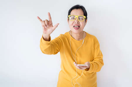 Photo pour Senior asian woman listening to music with earphone,Elderly female using smartphone feeling funny and enjoying,Relaxing time,Happy and smiling - image libre de droit