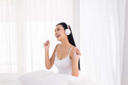 Photo for Beautiful happy woman singing and using headphone listening to music with dance in bedroom, Relaxing time - Royalty Free Image