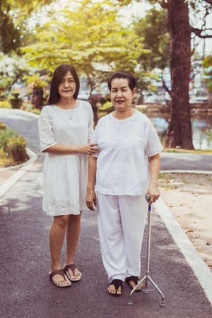 Photo pour Elderly Asian woman walking to do physical with stick at park,Daughter take care and support,Elderly social asia concept - image libre de droit