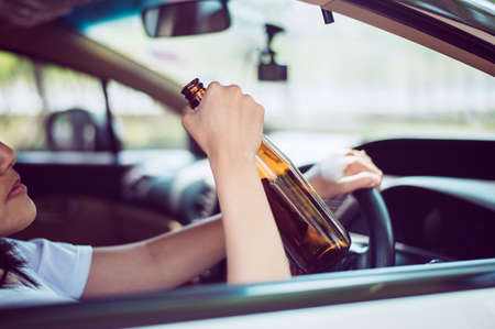 Drunk asian woman drinking alcohol while driving car on road,Women drive her car with a bottle of beer,Dangerous driving concept