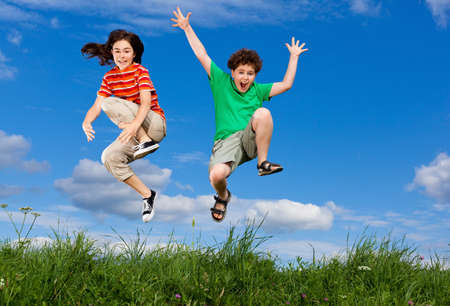 Girl and boy jumping outdoorの写真素材