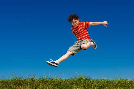 Photo pour Boy jumping, running against blue sky - image libre de droit