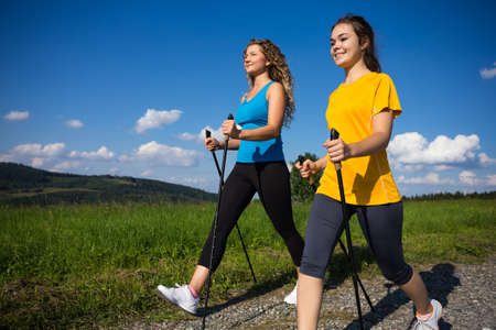 Photo for Nordic walking - active people working out outdoor - Royalty Free Image
