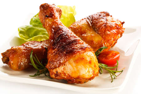 Close up of a plate of roasted chicken drumsticks