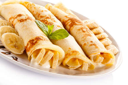 Crepes with bananas and cream on white background