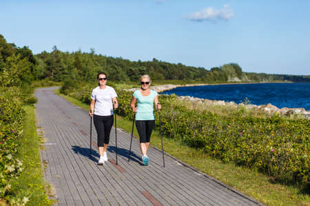 Photo for Nordic walking - active people working out in park - Royalty Free Image