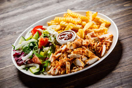 Foto de Kebab - grilled meat with french fries and vegetables - Imagen libre de derechos