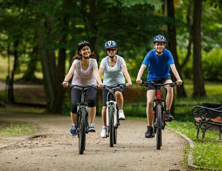 Photo pour Healthy lifestyle - people riding bicycles in city park - image libre de droit