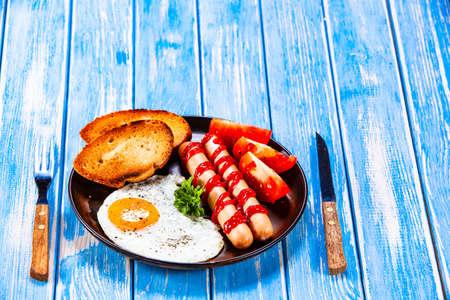 Photo pour English breakfast - fried egg, sausages, toasts and vegetables - image libre de droit