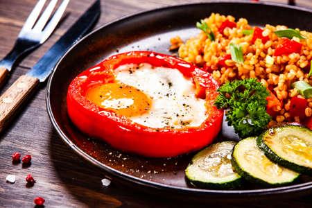 Photo pour Fried egg, groats and vegetables on wooden table - image libre de droit