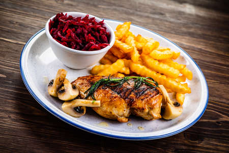 Photo pour Grilled chicken fillet with french fries and vegetables - image libre de droit