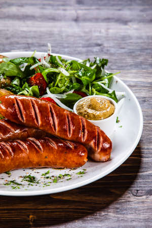 Photo pour Grilled sausages, baked potatoes and vegetables - image libre de droit