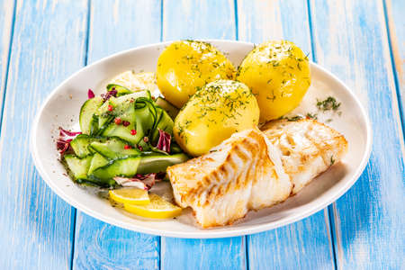 Photo pour Fried fish with potatoes and vegetable salad on white plate on blue planks - image libre de droit