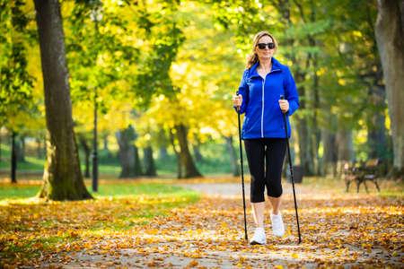 Photo pour Nordic walking - middle-age woman working out in city park - image libre de droit