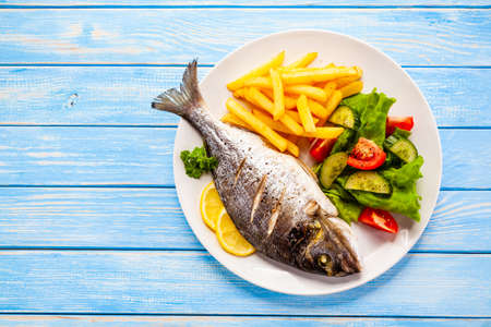 Photo pour Roast fish with french fries and vegetable on wooden background - image libre de droit