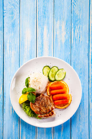 Foto de Roast steak with white rice and vegetables on wooden background - Imagen libre de derechos