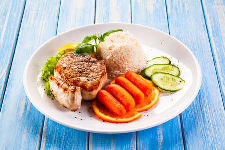 Photo pour Roast steak with white rice and vegetables on wooden background - image libre de droit