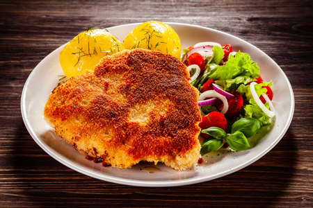 Foto de Schnitzel with boiled potatoes on timber background - Imagen libre de derechos