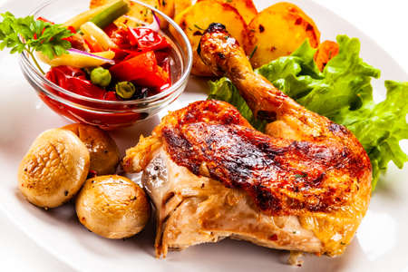 Photo pour Barbecued chicken leg with chips and vegetables on white background - image libre de droit