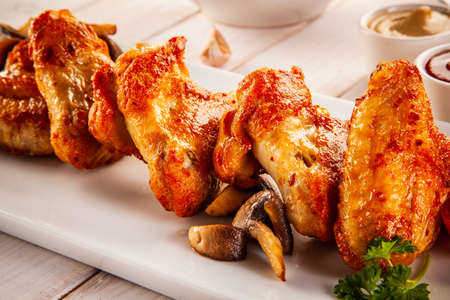 Photo pour Barbecued chicken wings with french fries and vegetable salad on timber - image libre de droit