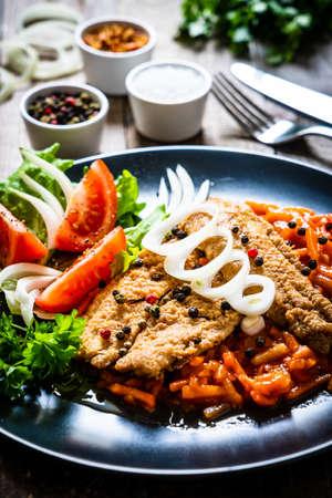 Photo pour Fish dish - fried fish fillet on vegetable sauce on wooden table - image libre de droit