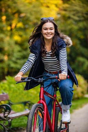 Photo for Urban biking - woman riding bike in city park - Royalty Free Image