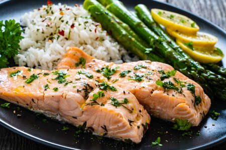 Foto de Steamed salmon fillet with basmati rice, asparagus and vegetables on wooden table - Imagen libre de derechos