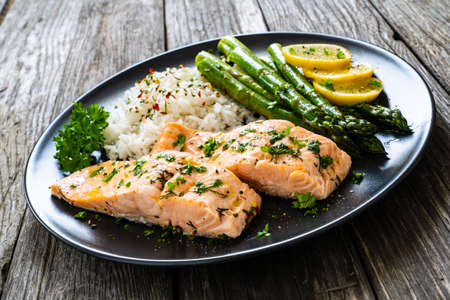Photo pour Steamed salmon fillet with basmati rice, asparagus and vegetables on wooden table - image libre de droit