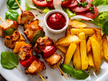 Photo pour Skewers - grilled meat with French fries and fresh vegetables on wooden background - image libre de droit